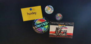 A selection of badges and stickers on a pinboard - Huxley, Rainbow Rovers, Whitehawk FC and Worthing & Beyond