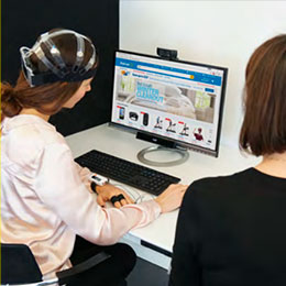 User research participant wearing an EEG headset at a screen during a testing session.