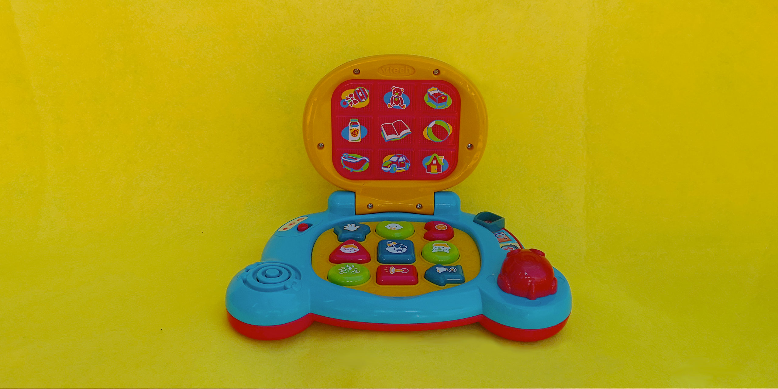 A child's laptop toy with icons on the screen