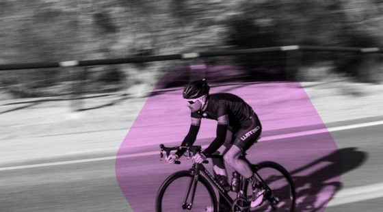 Sharp Wheels - Cyclist riding downhill in purple and greyscale brand colours, with a