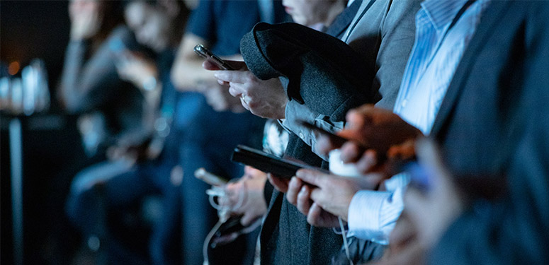 A crowd of people using their mobile phones