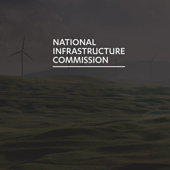 The National Infrastructure Commission logo superimposed on an image of Windmills on a Welsh hillside.