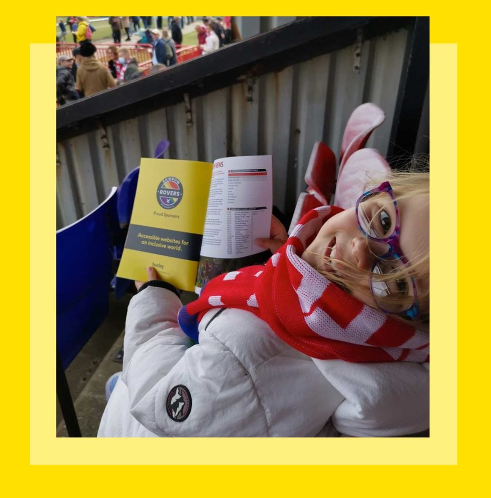Violet shows off an example of Huxley and Rainbow Rovers branding in a programme advert at Whitehawk FC