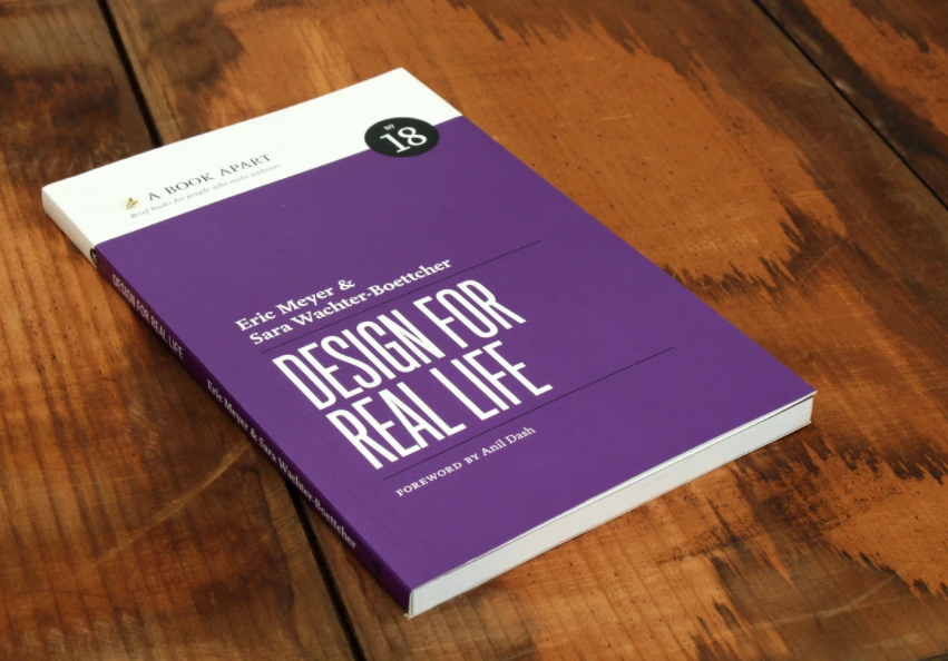 The cover of Design For Real Life. a simple purple cover, lying on a wooden surface