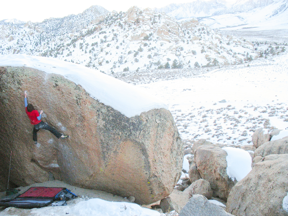 A photo of Steve climbing a boulder in what looks like a desert