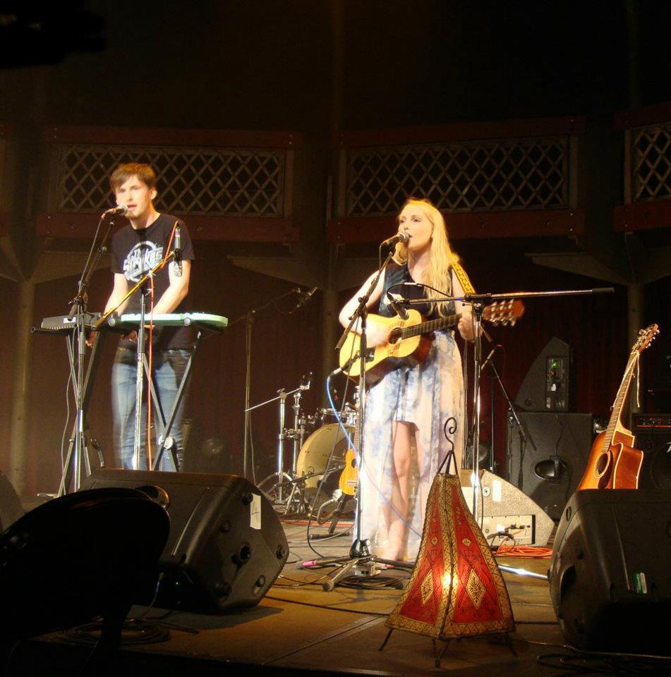 Hannah, a blonde woman, playing guitar and singing on a lit stage with someone on keyboards in the background.