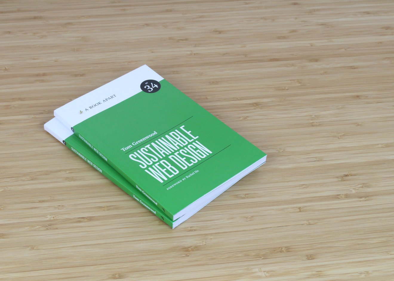 Two books with a green cover with white text: Tom Greenwood SUSTAINABLE WEB DESIGN; laying on a wooden surface
