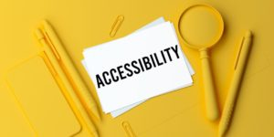 Pens, paperclips, a mobile phone, and a magnifying glass all spray painted yellow on a yellow surface, with a white paper that says ACCESSIBILITY in the centre