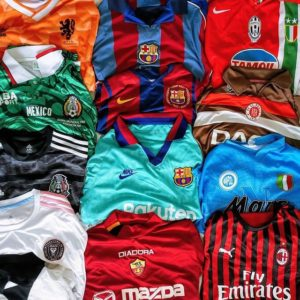 12 football shirts of different colours and teams squished together