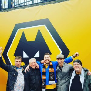 Dom with 4 other men looking happy in front of a wall with the Wolverhampton Wanderers logo