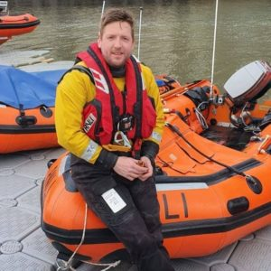 Dom sitting on a lifeboat with a life vest on